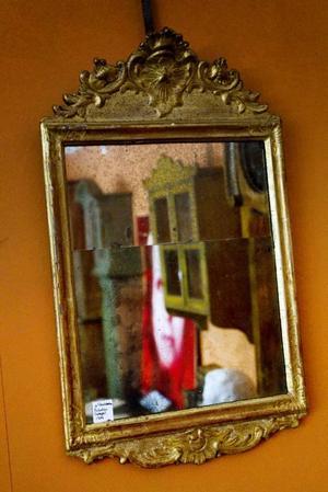 Utvecklingen står på golv och hänger på väggar i form av kerubprydda gjutjärnsurnor . En hallstämplad förgylld spegel från 1744, från Stockholms spegelmakarämbete.