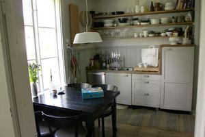 Gammalt kök med nya skåp och hyllor.