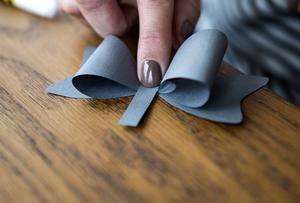3. Lägg den limmade delen ovanpå den rosettformade delen och använd det lilla pappersbandet för att hålla ihop dem.