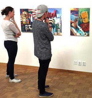 Besökare betraktar intresserat Alexander Lövgrens serie av målningar.