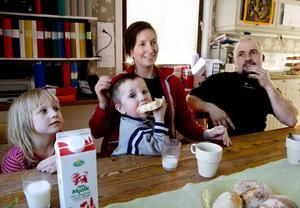 De minsta barnen, fyraåriga Lovisa och treårige Elias, fikar med mamma och pappa.