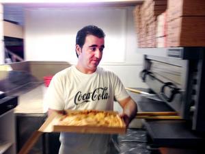 Knappt tio minuter tar det för Ghanem Majid att göra en Kebabpizza super. Kaloribomben som toppats med såväl kebab som pommes frites är den populäraste pizzan på Sörbygrillen.