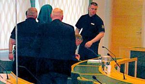 Häktad. Den häktade 16-åringen - med duk för huvudet för att inte synas - förs bort av häktesvakter, skymd av chefsåklagare Göran Kastlund med ryggen mot kameran.