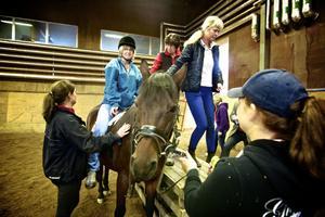 Yvonne Kronholm får hjälp att ta sig upp i sadeln. Bara det är ett träningspass.