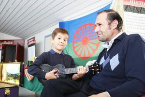 Erik Kalderas provar spela ukulele tillsammans med Maria Asp som också jobbar med utställningen.