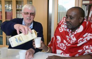 Bertil Wennberg häller upp lite av vaniljoghurten så hans gäst Rafael Reyet ole Moono får smaka.  Kanske kommer något liknande att produceras på det mejeri massajerna planerar att bygga i södra Tanzania.