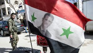 Flagga med president Bashar al-Assad och regeringssoldat i bakgrunden.