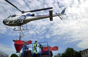 En helikopter fyller på tanken med myggbekämpningsmedel. Bilden är tagen vid ett tidigare besprutningstillfälle vid Dalälven.