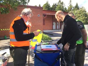 Samling vid lunchtid vid Pettersbergsskolan. Missing Peoples Jörgen Nylén räcker över den gula västen  till Marcus Sjöqvist, den sist anlände av de 36 frivilliga i sökandet.