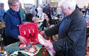 Gunnel Classon bjuder ut en del av sitt livsverk. Gudrun Granqvist tittar på en av hennes broderade julbonader. FOTO: KRISTINA VAHLBERG
