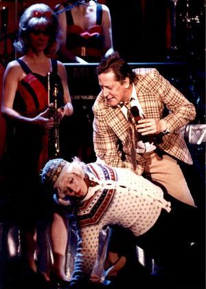 Lasse Brandebys (1945–2011) karaktär Kurt Olsson figurerade flitigt i både tv, radio och på scen. Här under ett uppträdande med damorkestern 1990.