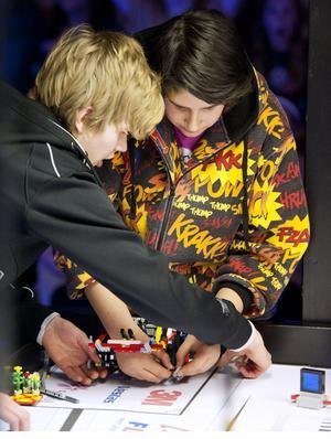 Martin Granberg och Roger Görceegiz i Maserskolans lag snabbreparerar roboten under tävlingens gång.