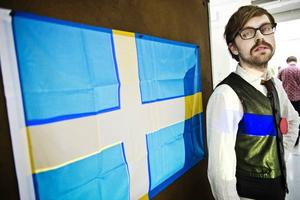 """UTMANAR. """"Ett försök att upphäva den svenska nationalismen"""". Utanför Konstfack har han hissat en prasslig presenning i flaggstången. Inne på utställningen visar konststudenten Joakim Forsgren från Skutskär en svensk flagga med färger i andra nyanser."""