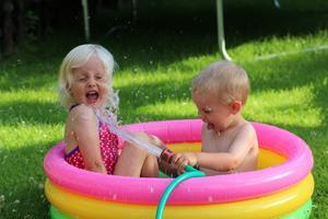 Lillebror Sam tycker det är fantastiskt roligt att blöta ner storasyster Leah.