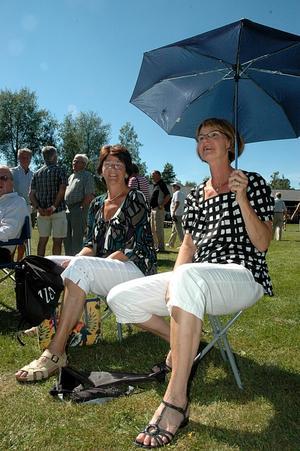 SKUGGA. Carina Björnesparr, Västerås, och Maud Sörehall, Vaxholm, skräms inte av värmen utan spänner upp paraplyer för att få skugga. De tycker att dragspelsmusik hör sommaren till och hoppas att dragspelsstämman återkommer nästa år.