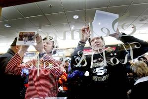 Joakim Bergman och Daniel Berlin skriver autografer mot kafé Selmas fönster.