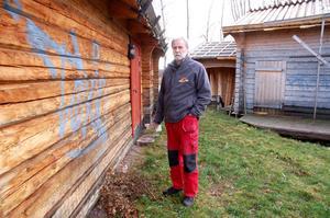 Olle Berglund är upprörd över att någon klottrat på timmerbyggnaderna.