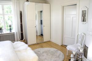 Vitt, beige och grått varvas i sovrummet. Detaljer i silver och fluffiga kuddar och plädar skapar en ombonad känsla. I hörnet står en gammal vacker vitglansig kakelugn.