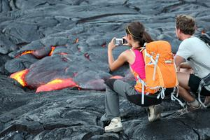 Turister fotar lavan vid en av världens mest aktiva vulkaner, Kilauea, Hawaii.