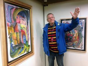 Björn Ståbi vid två av sina tavlor, Naturens försvar och Ljusglimt