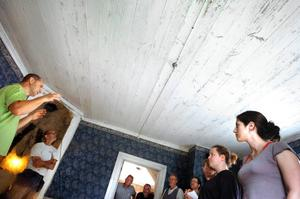 """Arkivarien Gabor Pasztor berättar om bevarandet av gamla tapeter innan kursdeltagarna sätter igång med arbetet i det """"blå rummet"""". Tapeten från 20-talet ska sparas för att visa prästgårdens utseende från den tid då den senast var bebodd."""