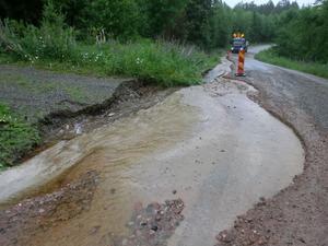 Efter 70 mm regn såg vägen till Dala-Floda genom Skeberg ut så här på måndagsmorgonen. Genom byn Gropen gick den med nöd och näppe att ta sig fram på ena sidan av vattenmassorna när Peab dök upp för att ta hand om skadorna.