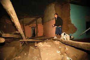 En boende i Talca går genom ruinerna av ett hus som skadats kraftigt i jordbävningen.