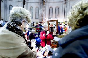 Barbro Ellebo besökte mässan med en väninna. Här provar hon stickade mössor som hantverkaren Ulla Johansson har gjort. Ulla lärde sig sticka av sin mormor när hon var fyra år – med hårnålar.