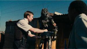 Wikus van der Merwe (Sharlto Copley) sätts att leda tvångsevakueringen av utomjordingarna. Foto: TriStar Pictures