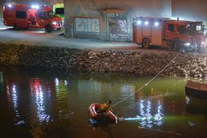 Dykare i arbete med bärgning under motorvägsbron.