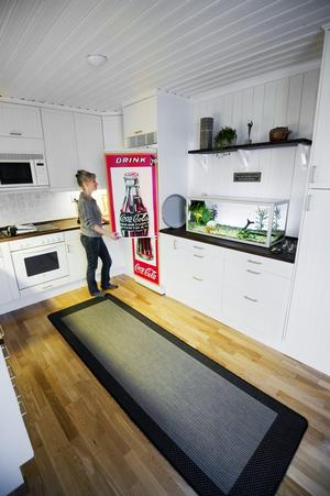 Kylskåpet är köksavdelningens stora prydnad. Det är täckt av en plastfilm som Gerts företag tillverkat. Jenny var först lite tveksam till coca-colaflaskan som budskap men tycker numera att den tillför färg till köket. Vilket även akvariefiskarna gör.