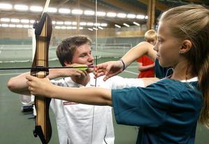 Tove Gärdin testar på bågskytte, här instrueras hon av Oskar Kårström.