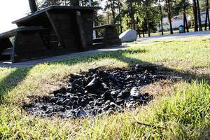 Rester efter en eld på gräsmattan vid Svedvi rastplats.