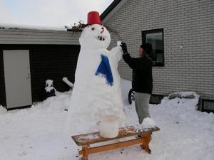 Evelina gjorde en stor fin snögubbe av den första snön. Den vinkar glatt åt alla som åker förbi och när det skymmer till kvällen så håller han ett ljus i handen som lyser.