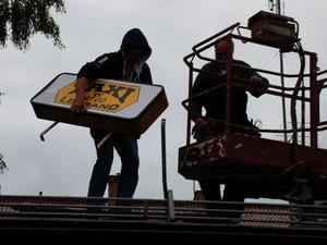 Skylten tas ner. Här tas skylten ned efter det att beslutet var taget att Leksands Taxi lägger ner verksamheten. Nu är frågetecknen många kring hur taxiverksamheten ska fungera på sikt för privatpersoner och företag i Leksand.
