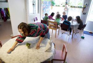Therese Rotvall passar på att städa bordet efter lunchen medan Adam, Ella, Olle, Elissa, Ella, Isak och Siri sysselsätter sig själva vid pysselbordet.