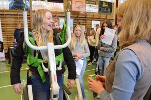 Ett lyft för utbildningar. – Åh! Det är jätte-läskigt att lyftas upp och åka bakåt, säger Linna Elmik Johansson. Hon testar den stå-lyft som arbetsterapeut Erica Zedig demonstrerar på gymnasiemässan.