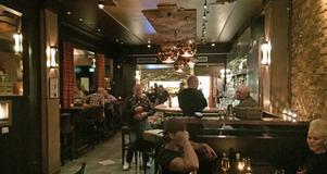 Ja, det är såklart stamkunden Berndt Erlandsson i mitten av bilden. På väg att sätta sig på sin vanliga plats i hörnet av baren.