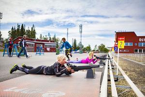Elsa Tänglander och Lydia Hägg Eveby i en tajt kamp på skyttebanan medan Alexander Serdaris lägger på en rem i bakgrunden.