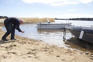 Per-Yngve Velander fotograferar fotspår i sanden för att kunna matcha mot eventuella misstänkta.