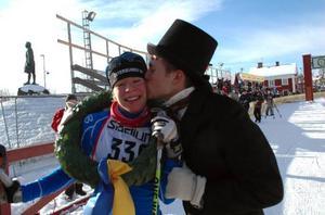 Maria Rydqvist, Östersunds SK, gratuleras av kransmasen Jonas Nilsson sedan hon vunnit damklassen i SkejtVasan. Foto: Media/Vasaloppet