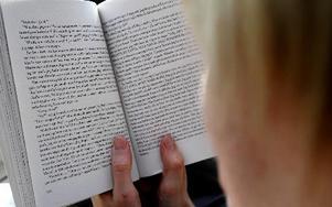 Kvinna läser en bok. Foto: Hasse Holmberg, SCANPIX
