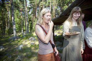 Anna Hellgren smakade på köttet som lagats i jordgropen i vikingabyn i Årsunda. Vikingen Helga skar upp det nykokta köttet.