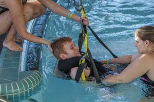 Lisa Lindgren och Linda Perslive hjälper Johan Persson att komma ner i vattnet.