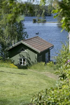 Nere vid sjön ligger ett båthus, som med bord och kylskåp, som gjort för sena pokerpartier och dartspel.