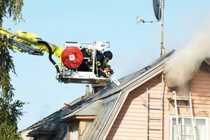 Räddningstjänsten sågade upp taket på en grannfastighet för att komma åt elden som spridit sig dit.