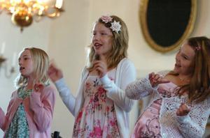Moa, Nora och Emma sjunger och dansar.