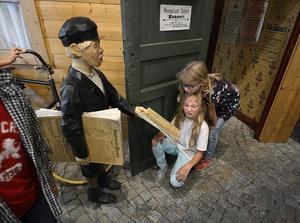 Freja Sigren och Alica Lindqvist kollar in tidningspojken på museet.