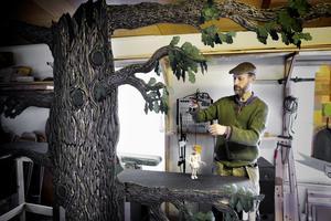 """Uråldrigt träd. I den grönskande kulissen ska Georgy våga möta ormen för att rädda prinsessan. Dockan har varit en del av Uwes liv länge. """"Med honom är jag väldigt förtrogen"""", säger Uwe. Foto: Mattias Holgersson"""