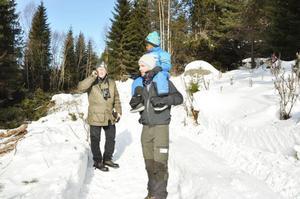 Håkan Blomqvist och Andreas Karlberg från länsstyrelsen, med sonen Mark på axlarna, går längs med den gamla landsvägen och kikar på de gläntor som SCA har röjt fram för att gynna den sällsynta fjärilen Trolldruvemätare.